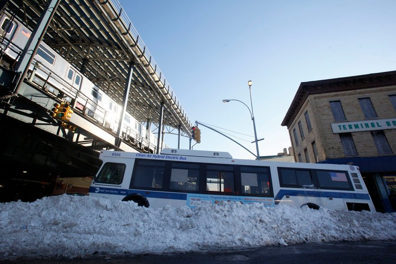 A city bus sits stranded in the street Tuesday amid snowbanks clogging a neighborhood in Brooklyn. On local highways, more than 1,000 abandoned vehicles had to be removed.