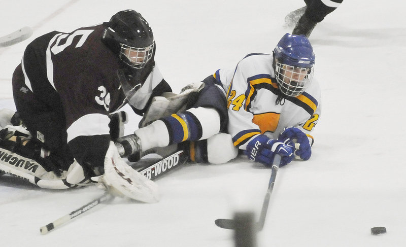 Mitch Tapley of Falmouth reaches for the puck Wednesday while sliding into Mike Amarone, the goalie for North Haven, Conn. The holiday tournament gives Maine teams the opportunity to test themselves against others.