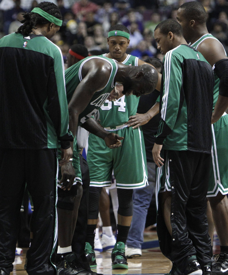 Kevin Garnett is surrounded by teammates while grimacing in pain Wednesday night in the first quarter of the Boston Celtics' 104-92 loss to the Detroit Pistons.