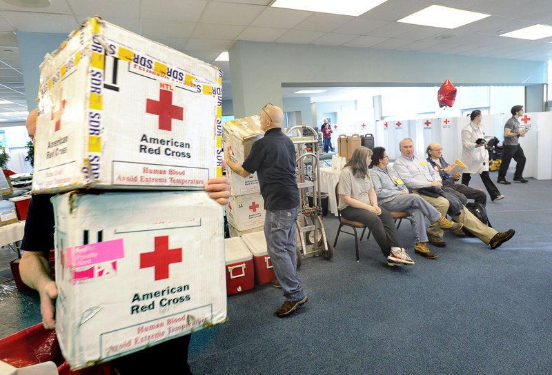 Workers distribute transport boxes as the first four donors wait their turn to give blood Thursday. The drive in Portland attracted some first-time donors, and others who had already given gallons.