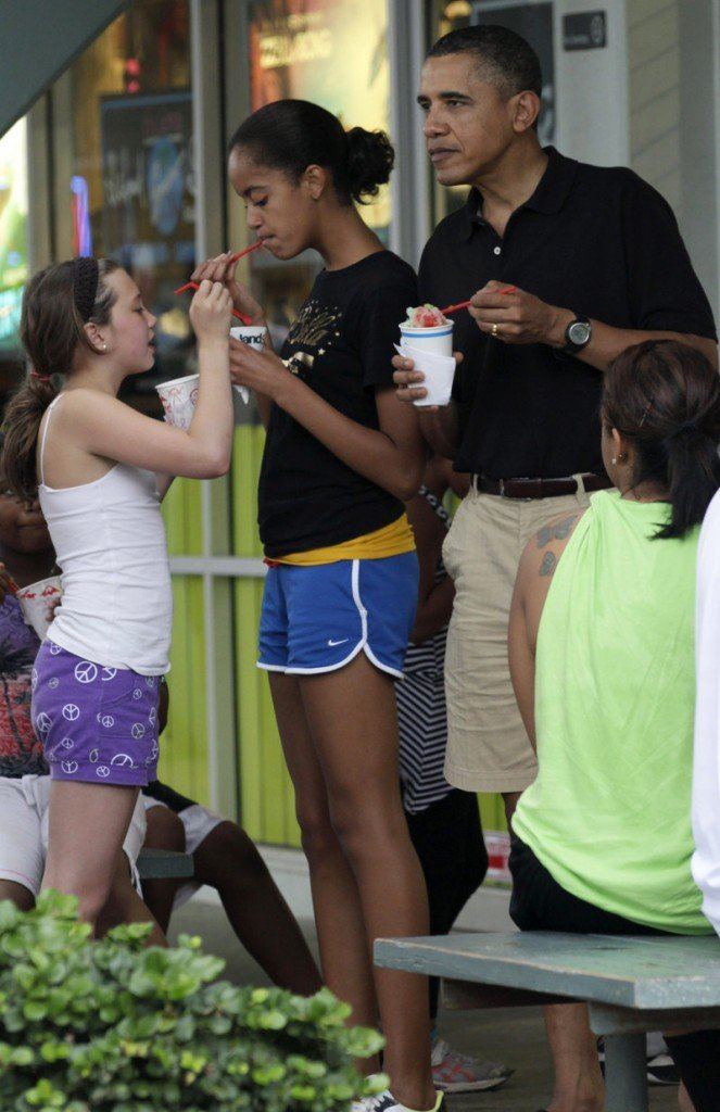President Obama, his daughter Malia, second from left, and other family members and friends eat shave ice earlier this week at Island Snow at Kailua Beach Center while on vacation in Kailua, Hawaii.