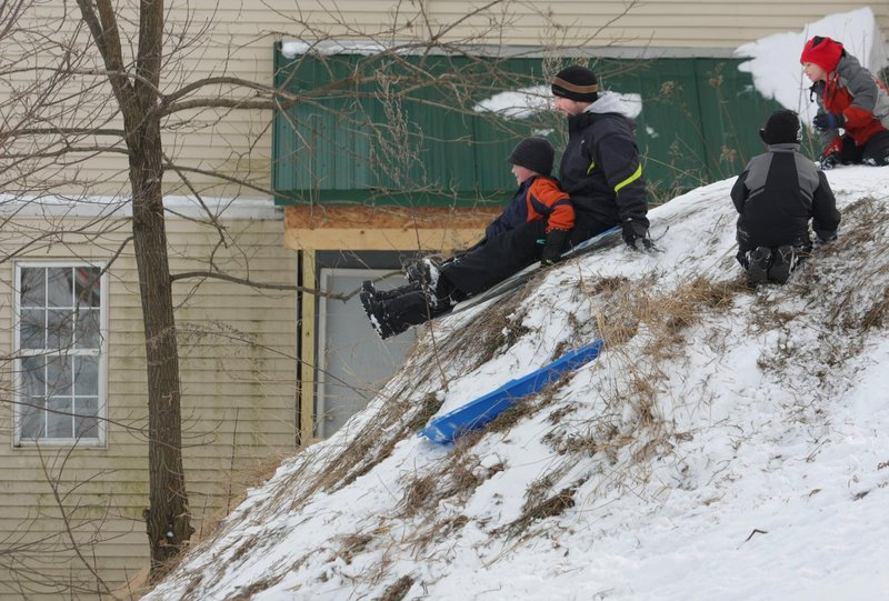 Chet Hanscom of Benton and his 8-year-old son Christian take off on a steep sledding run on a hill off Sherwin Street in Waterville on Thursday. The Hanscoms were enjoying the day on the local hill with family and friends.