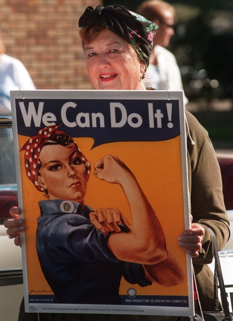 "Geraldine Doyle poses with the famous World War II ""Rosie the Riveter"" poster that was made with her likeness."