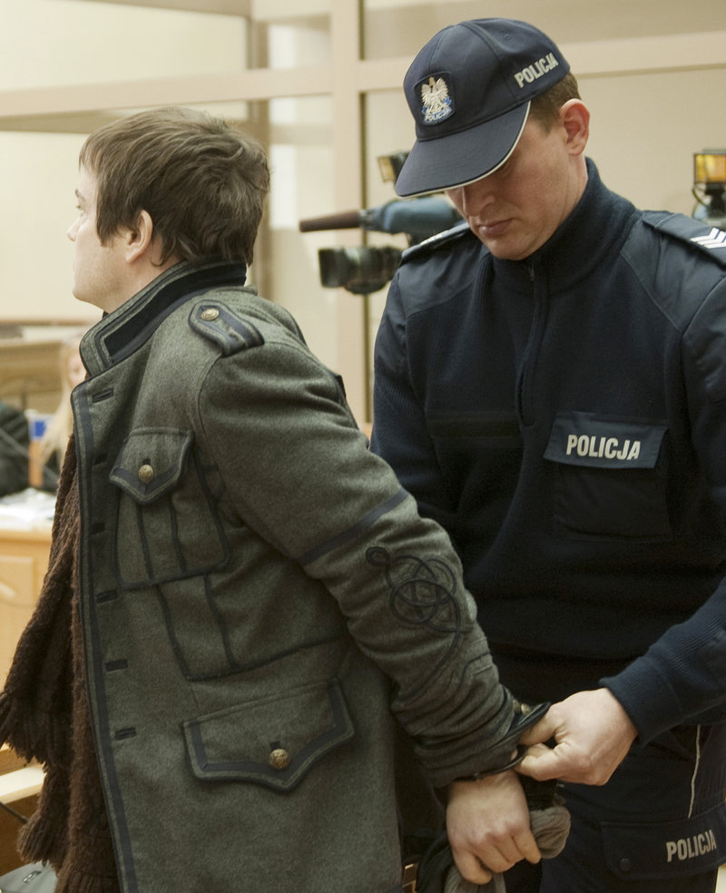 A police officer removes handcuffs from Anders Hogstrom on Thursday in Krakow, Poland. A court approved a prison term for Hogstrom for his role in the theft of the Auschwitz sign.