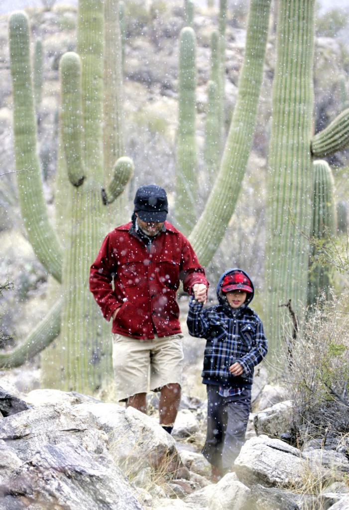 Jon Benjamin, left, walks through snow flurries with his son Judah Benjamin, 7, on the Finger Rock Trail near Tucson, Ariz., on Thursday. The National Weather Service issued a blizzard warning for eastern and southeastern Arizona.