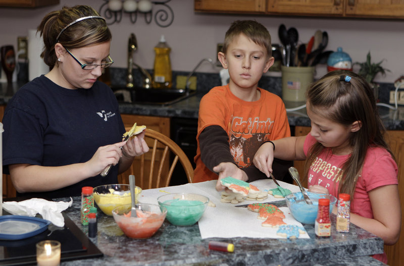 Tanner Hisey, center, puts icing on Christmas cookies with his sister Siera, right, and half-sister Tyler Smith in their home near Clyde, Ohio. Tanner, 12, and Tyler, 17, are among 35 children who live within a few miles of this small farming town and have been struck by cancer in the last decade.