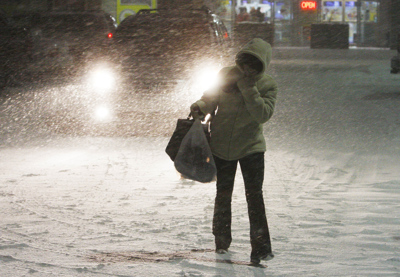 Elizabeth Kistoglou of Watertown, Mass., walks through a heavy snowfall as she leaves work at Shoppers World in the Boston suburb of Framingham, Mass., Sunday. Maine is expected to receive 12 to 18 inches of snow from the blizzard working its way up the East Coast.