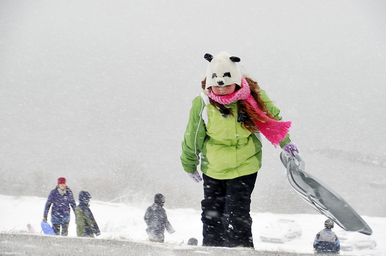 Adara Bankhead, 10, of Portland hangs on to her sled in the fierce wind and snow today on the Eastern Prom as she climbs the hill for another run. She was there with her family.