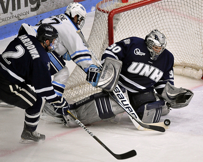 UMaine's Matt Mangene tries to slip the puck past UNH goalie Matt DiGirolamo as defenseman Connor Hardowa closes in. The Black Bears held a 3-1 lead entering the third period before the Wildcats rallied for a 4-3 win in OT.