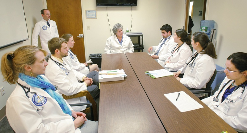 Elisabeth DelPrete, D.O., center, chair of the University of New England's department of family medicine, is shown meeting last year with first-year medical students. Legislators would be wise to continue funding the Doctors for Maine's Future program, which helps Maine students pay for medical school.