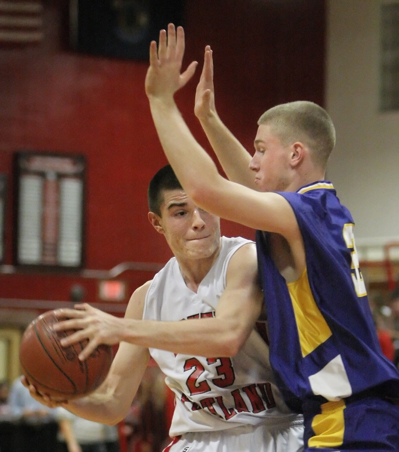 Vukasin Vignjevic of South Portland looks to pass Friday night while under pressure from Nick Burns of Cheverus during Cheverus 63-46 victory at Beal Gym in South Portland.