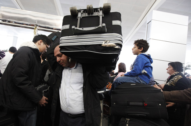 A man carries his luggage at the departure terminal of Cairo's international airport today, where thousands seek to flee the unrest in Egypt and countries around the world send in planes to fly their citizens out.
