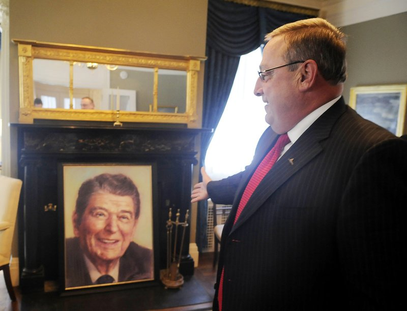 In the Blaine House on Wednesday, Gov. Paul LePage shows off a portrait of former President Ronald Reagan that he bought at the Mardenâ s in Waterville for $64.