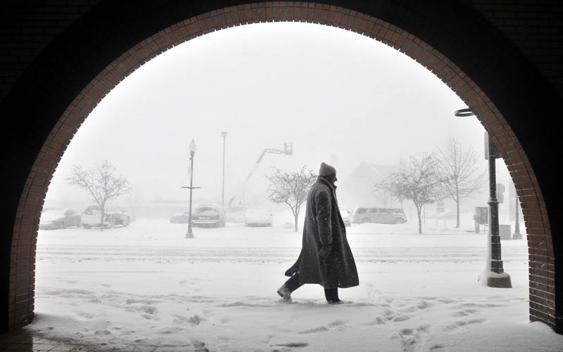 Staff photo by Michael G. Seamans Tony Karter walks through the heavy snow on Main Street in Waterville Wednesday morning.