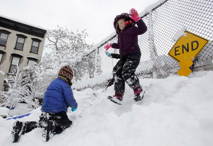 While her brother Seamus Lavelle, 4, left, climbs up, Sinead Lavelle, 5, jumps down a snow hill on their dead end street in Brooklyn, N.Y., today.