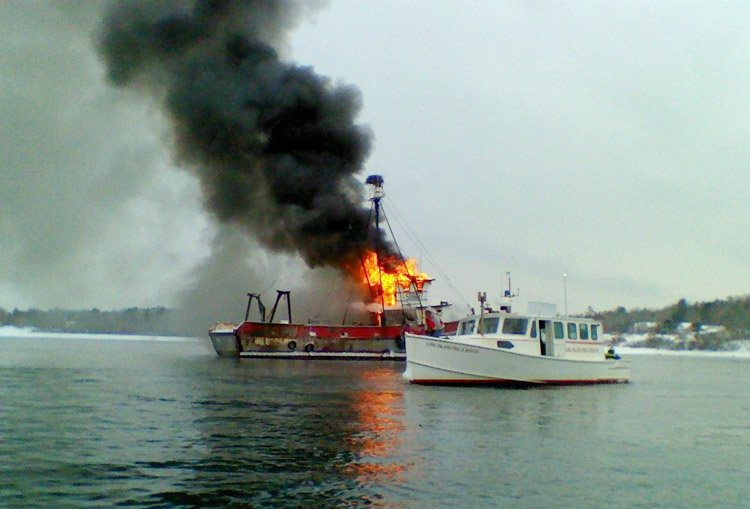 The 67-foot Deborah Lee burns at its mooring near Great Chebeague Island. Coast Guard crews and local responders are currently working to put out the fire and ensure there is no pollutioin. Photo by Coast Guard Station South Portland.