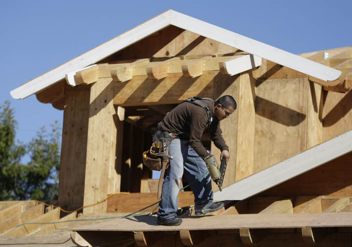 A carpenter works on the roof of a new home recently in Palo Alto, Calif. Builders of new homes are struggling to compete in markets saturated foreclosures.