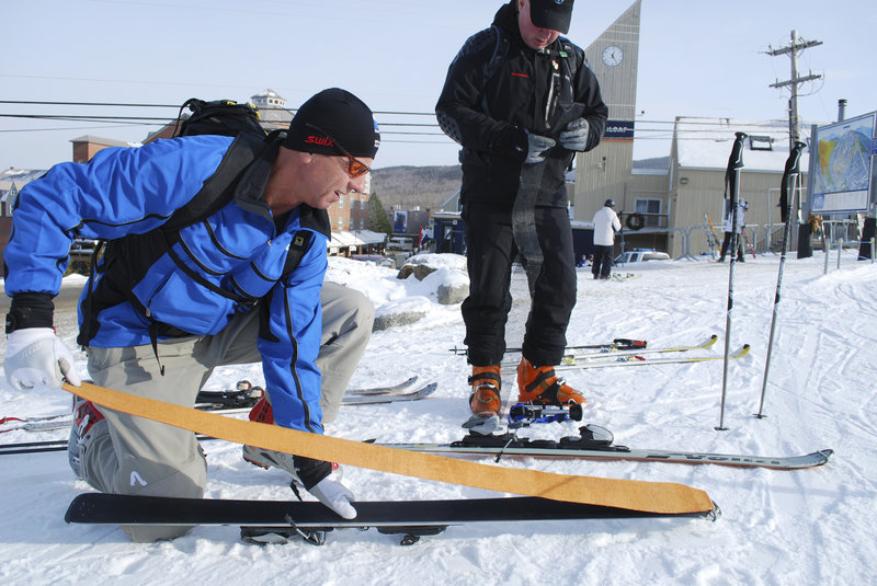 Cooper Friend affixes synthetic skins to skis before a training run with Warren Cook.