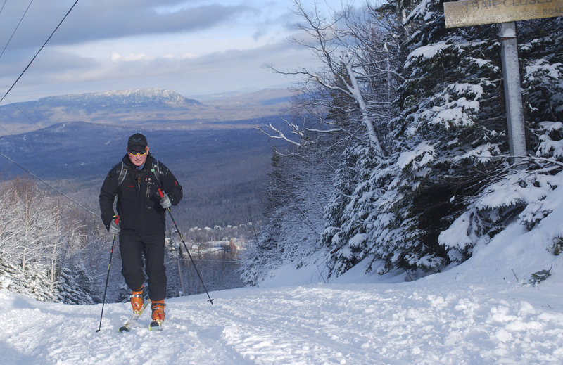 Warren Cook of Kingfield ascends an access road at Sugarloaf recently, with Bigelow Mountain in the background, wearing skis with Alpine touring bindings and skins. Cook, a former ski area owner and manager, has helped give this type of skiing, also called randonnee, a resurgence in Maine.