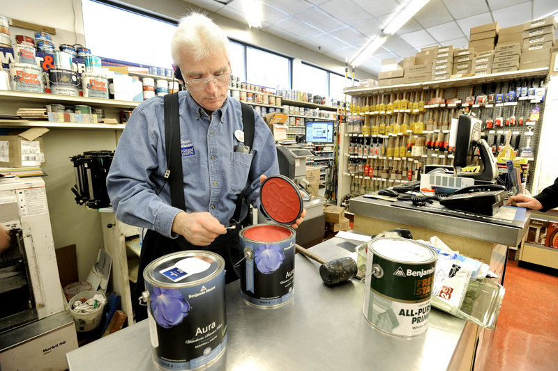 Kevin Coolbrith checks the color after he mixes paint at Ace Maine Hardware store in Portland. Paint producers could be required to pay for collection and disposal of used cans if the Legislature acts on a recommendation.