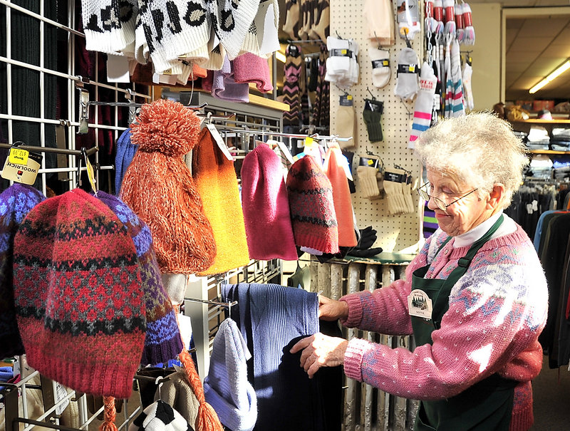 "Dottie Hinds straightens items in the women's clothing department at the Renys in Bath. She has been with the company for 14 years. ""They are wonderful people to work with,"" she said."