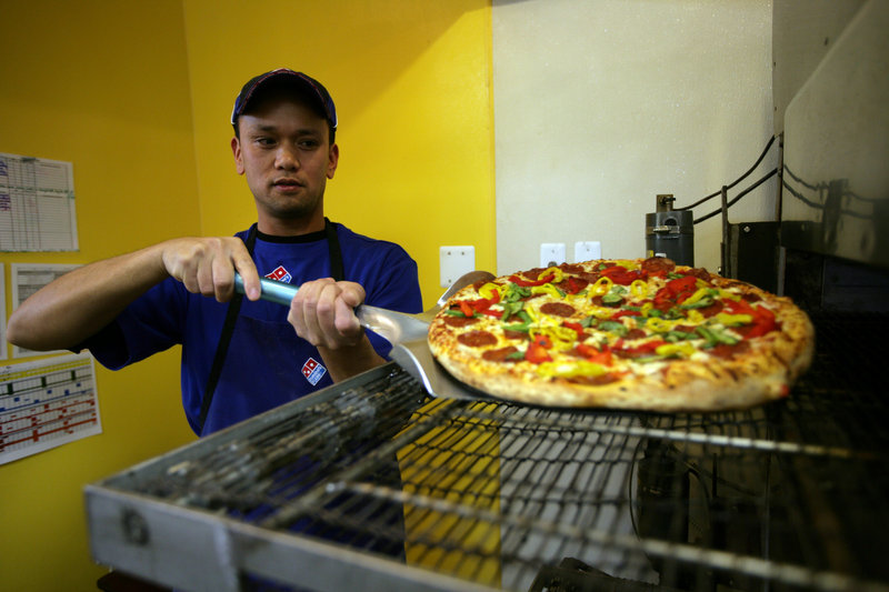 West Lopez of Farmington Hills, Mich., takes a chicken pineapple pizza from the oven at Domino's Pizza there.