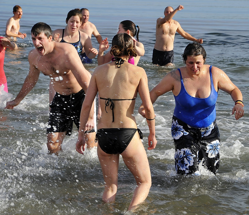Participants react to the cold water as about 40 people take the Natural Resources Council of Maine-sponsored Polar Plunge at East End Beach on Friday.