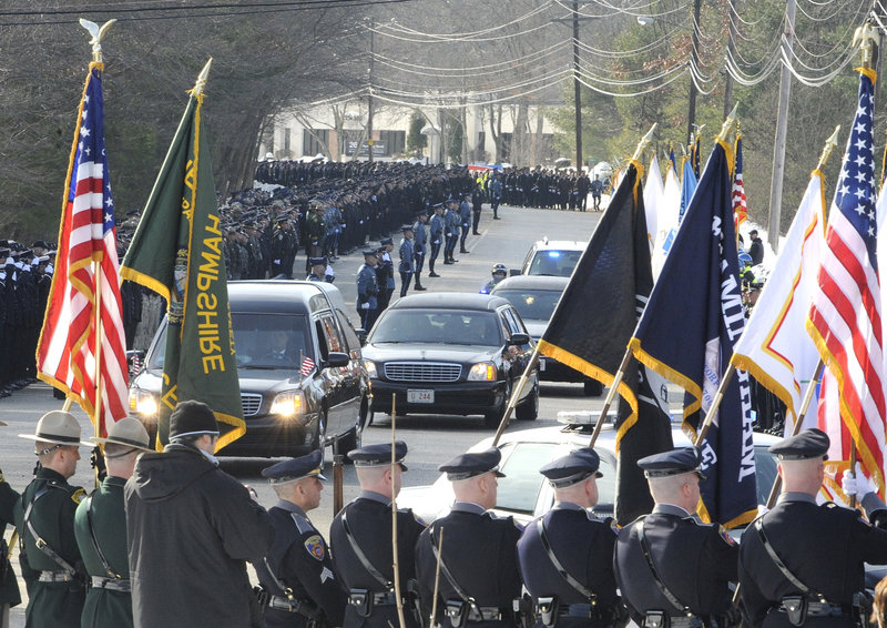 The Associated Press The funeral procession for John Maguire, a Woburn, Mass., police officer, heads toward the Shriners Auditorium on Friday in Wilmington, Mass. Maguire was shot after responding to an armed robbery attempt and later died of his wounds. Maguire, 60, was a 34-year veteran of the department and the son of the city's former police chief.