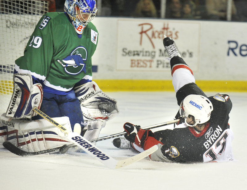 Paul Byron of the Portland Pirates slides into Connecticut goalie Chad Johnson after being taken down from behind on a breakaway Friday. Byron was given a penalty shot, which he converted. Connecticut won 5-4 in overtime at the Cumberland County Civic Center.