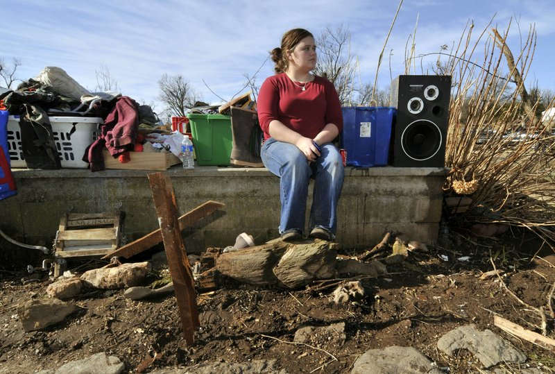 Paige Sisemore, 18, sits on the foundation of a home behind a makeshift cross made from debris after a tornado tore through the small town of Cincinnati, Ark., on Friday. The storm killed three people in Arkansas while three more people died in Missouri.