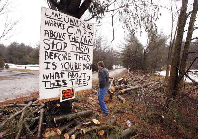 Michael Breton walks past a sign he put up last March after a crew hired by CMP felled trees on his property off Falmouth Road in Windham. Under PUC rules, CMP needs to provide direct notice at least 30 days before trimming.