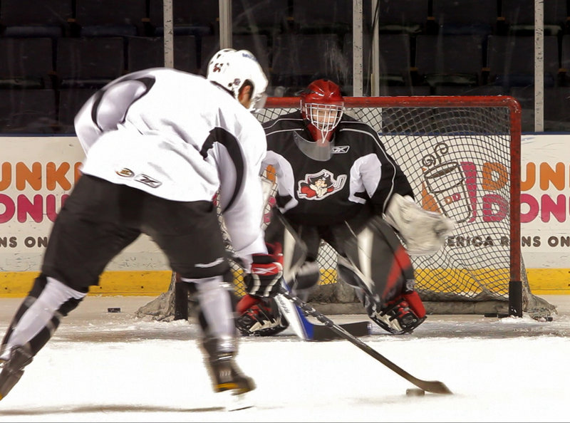 Reporter Bob Keyes survives a stint in the goal during a Portland Pirates practice.
