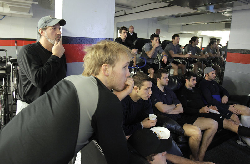 Reporter Bob Keyes, far left, listens during a pre-practice meeting with the Portland Pirates before taking the ice.