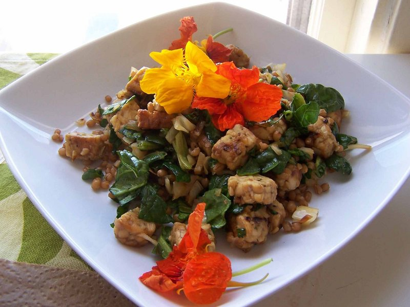 Sweet and spicy tempeh salad with nasturtium garnish.