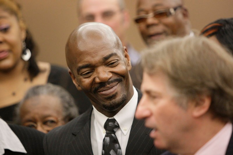 Cornelius Dupree Jr., 51, center, smiles as attorney Barry Scheck, right, speaks in Dallas on Tuesday. Dupree – who could have been paroled earlier had he not maintained his innocence in a rape and robbery – served more time for a crime he didn't commit than any other Texas inmate exonerated by DNA evidence.