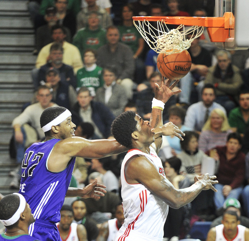 DeShawn Sims of the Maine Red Claws is fouled by Walter Sharpe of the Dakota Wizards while going up for a shot Thursday night. Maine won 99-95 in overtime at the Expo.