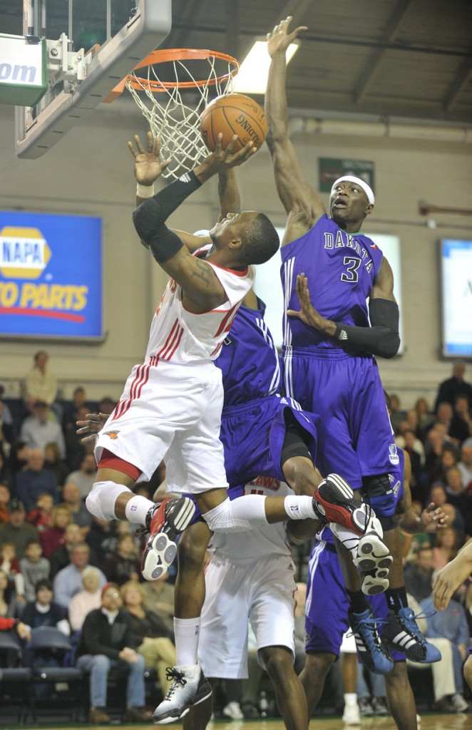 Kenny Hayes of the Maine Red Claws takes the ball to the basket Friday night as Hamady N Diaye of the Dakota Wizards, right, attempts to swat it away. Dakota won, 93-70.