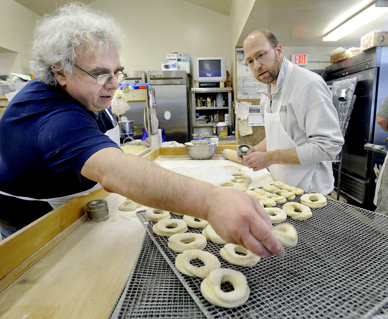 Rick Fournier, left, owner of Tony's Donuts, shows Ray Routhier how to cut doughnuts.
