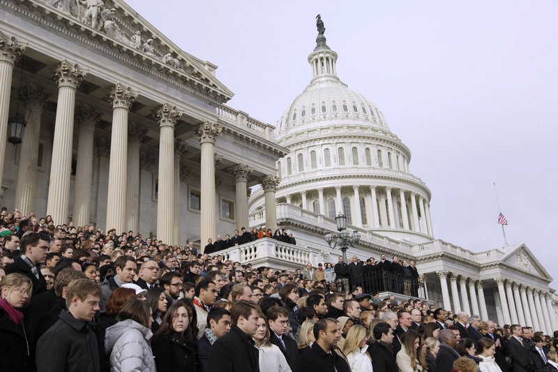 Members of Congress and their staffs observe a moment of silence for Rep. Gabrielle Giffords, D-Ariz., and other shooting victims Monday on the East Steps of the Capitol. Giffords, who was shot in the head at close range, remained hospitalized in critical condition.