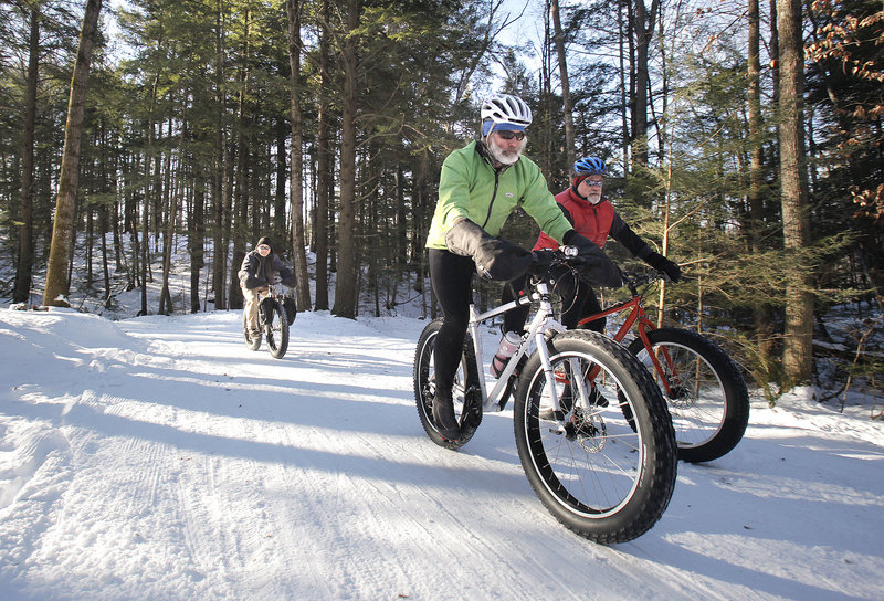 Jeff Clarke, left, Glenn Fenlason, center, and Brian Alexander ride winter bikes in the Quarry Road Recreation Area in Waterville. The bikes use fatter tires for better traction in the snow.