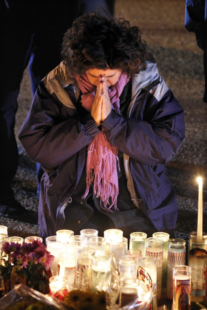 A woman prays Monday at the memorial in front of the University Medical Center in Tucson, Ariz.