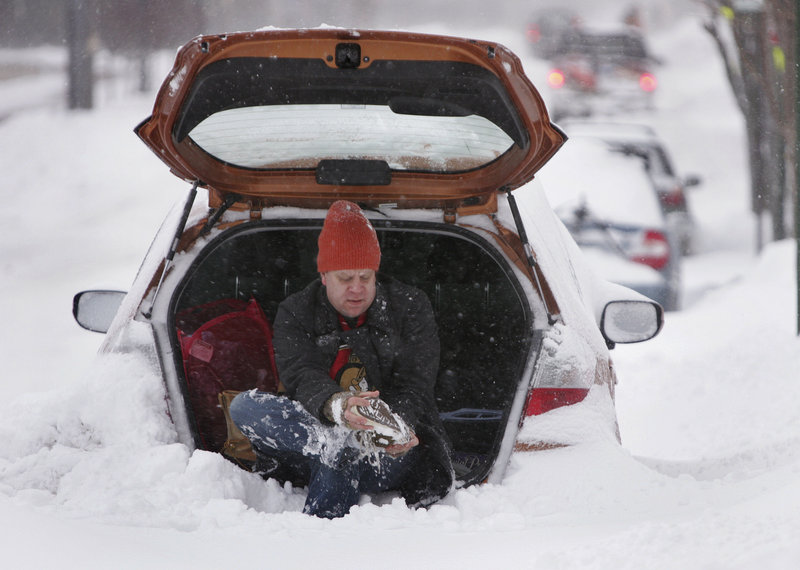 Josh Denkmore of Portland changes his shoes to get ready to dig out his car on Cumberland Avenue amid Wednesday's snowstorm.