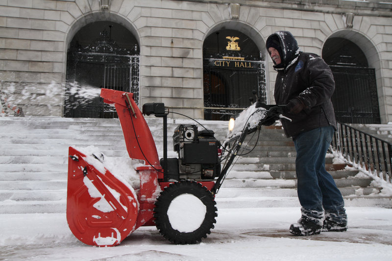 City employee Henry Fontaine clears snow from the steps of Portland City Hall on Wednesday.