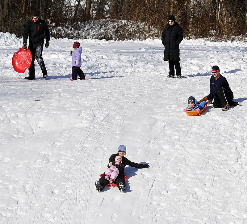 Sledders queue up to try the sledding hill at Fort Williams Park in Cape Elizabeth.