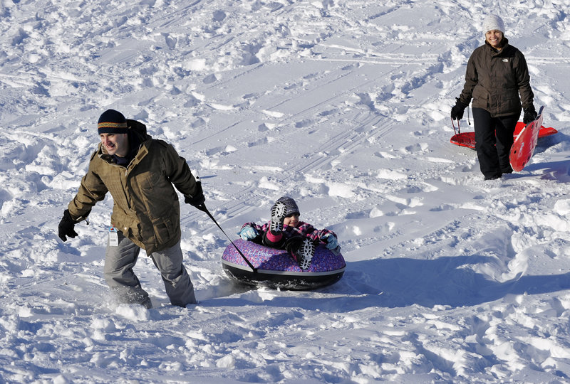 Matt and Carmensol Kesselhout of South Portland enjoy one of the several sledding hills at Fort Williams Park with their children Maximo, 8, and Isabel, 6, who is being pulled up the hill by her father.