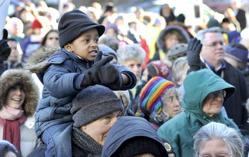 Three-year-old Dmitri O'Sullivan is perched atop the shoulders of Bob Bahm from Falmouth as they listen to speeches at Portland City Hall during the Martin Luther King Jr. Day march and rally for justice in Portland on Monday.