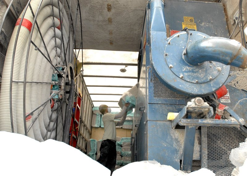 Sophim Kadek of Warm Tech Solutions feeds insulation into a blower machine that pumped the material to the crawl space of a house in Richmond. Federal stimulus money helped create strong demand for energy improvements.