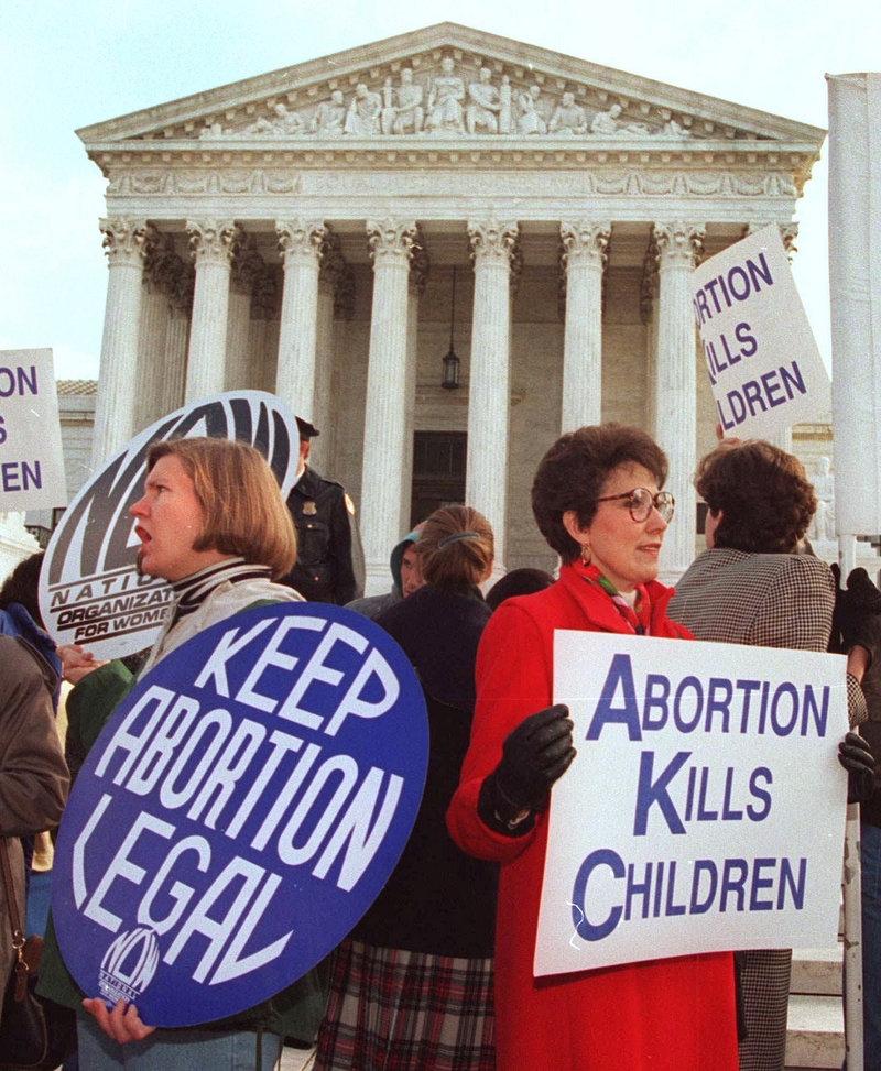 Protesters on both sides of the abortion issue hold signs outside the U.S. Supreme Court during the 2006 March for Life demonstration.