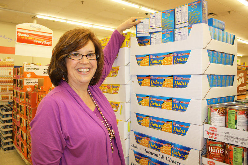 Erin Judge turns around boxes of macaroni and cheese at a Portland supermarket to show that the products contain partially hydrogenated oil. She' s asking other shoppers to join her Operation Rev