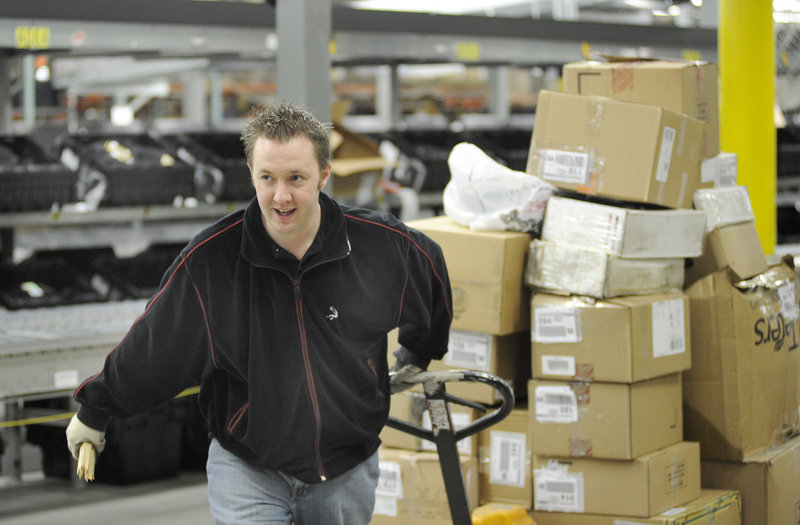 Kevin Kennie moves boxes at the Olympia Sports distribution center in Westbrook. The company employs about 2,000 people throughout the Northeast.
